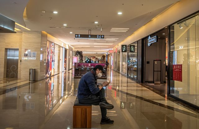 A man wearing a protective face mask sits in an almost empty mall in Beijing.