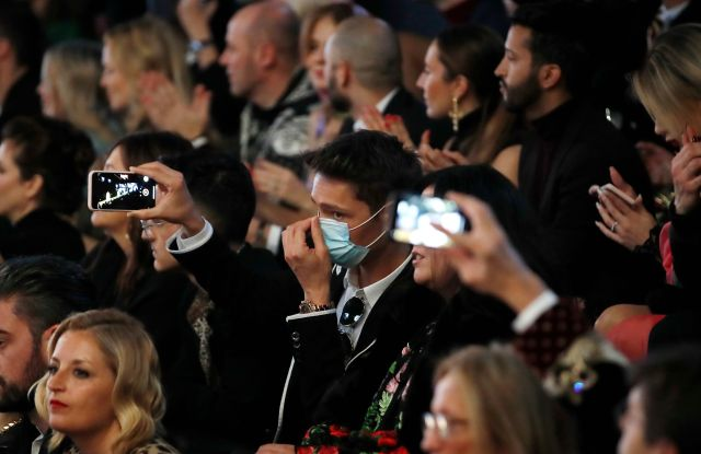 A man wearing a sanitary mask takes photos during the Dolce & Gabbana women's Fall Winter 2020-21 show, in Milan, Italy, . After Giorgio Armani's last-minute decision to show his latest collection in an empty theater due to concerns about the new virus, the rest of Milan's runway shows scheduled for Sunday are to go ahead as planned, fashion officials confirmedFashion F/W 20/21 Dolce & Gabbana, Milan, Italy - 23 Feb 2020