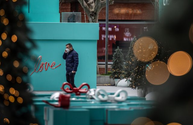 A man wearing a face mask walks past giant New Year and Christmas decoration outside a shopping mall in Shanghai, China.
