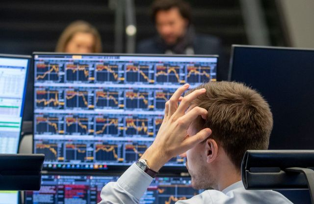 A broker scratches his head as he looks at his screens at the stock market in Frankfurt, GermanyStock Market, Frankfurt, Germany - 09 Mar 2020
