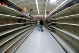Man shops in an aisle of mostly empty shelves in a Walmart in Cranberry Township, Pennsylvania.