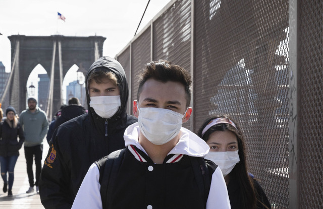 People wear masks as they cross the Brooklyn Bridge, in New YorkVirus Outbreak , New York, United States - 16 Mar 2020