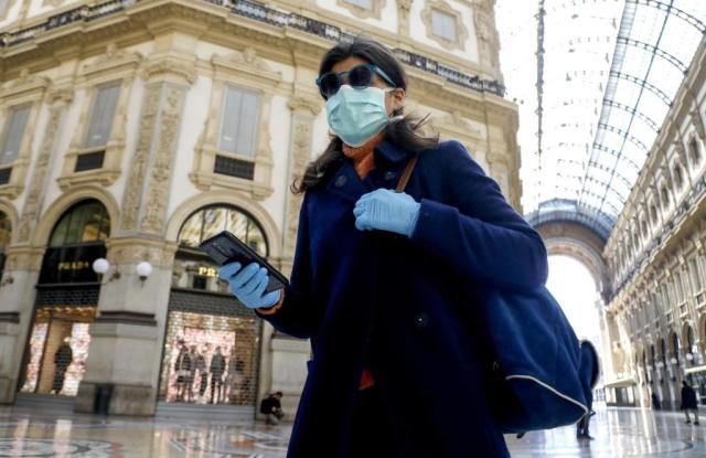 A woman wearing a face mask walks past the deserted Galleria Vittorio Emanuele II amid coronavirus outbreak, in Milan, Italy, 11 March 2020.Coronavirus in Italy, Milan - 11 Mar 2020