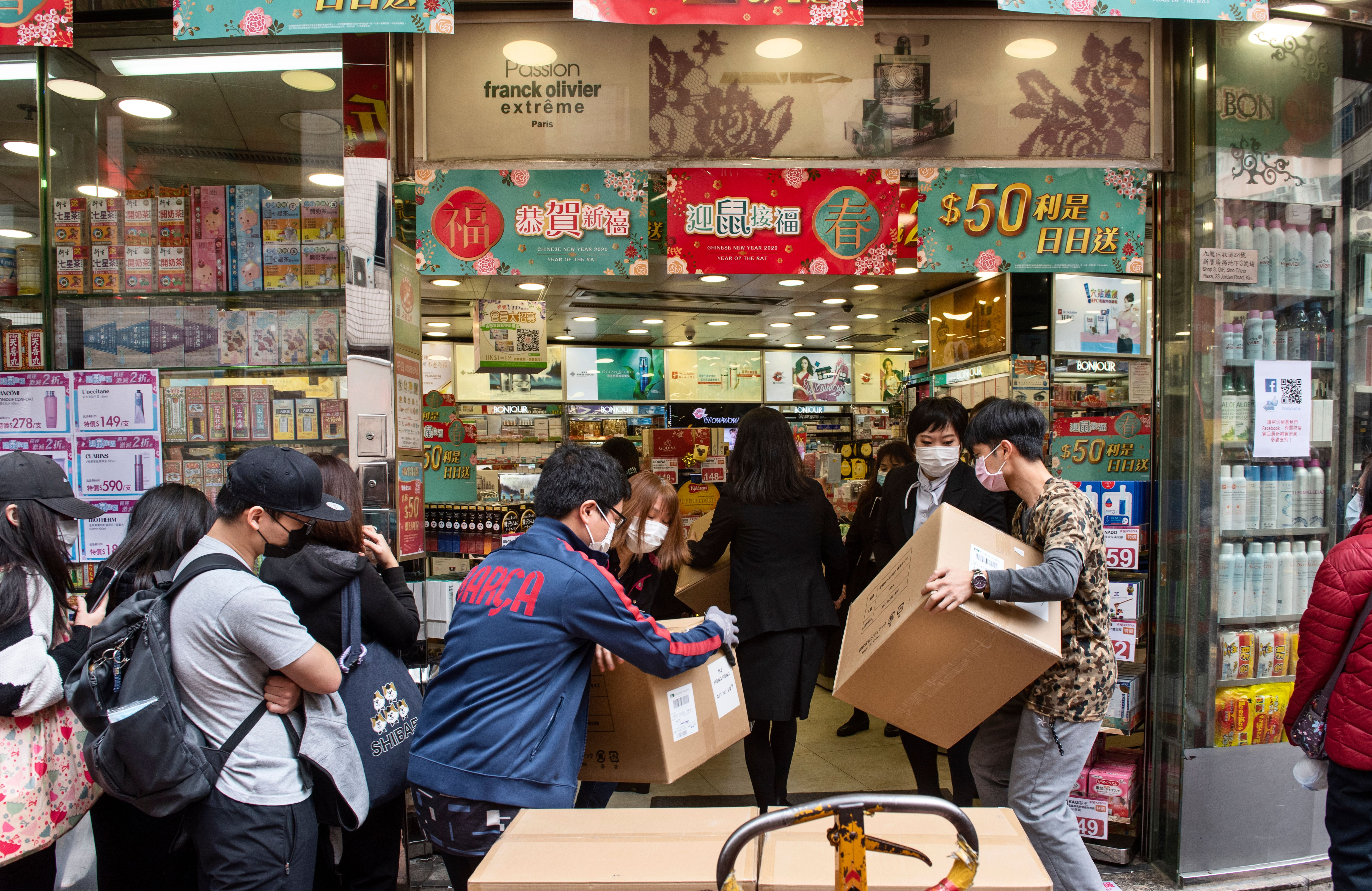 Employees at a cosmetic shop receive 460 boxes of face mask stock while customers wait in a line in Hong Kong.