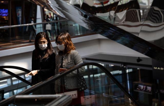 People wear face masks at a shopping mall in Hong Kong,