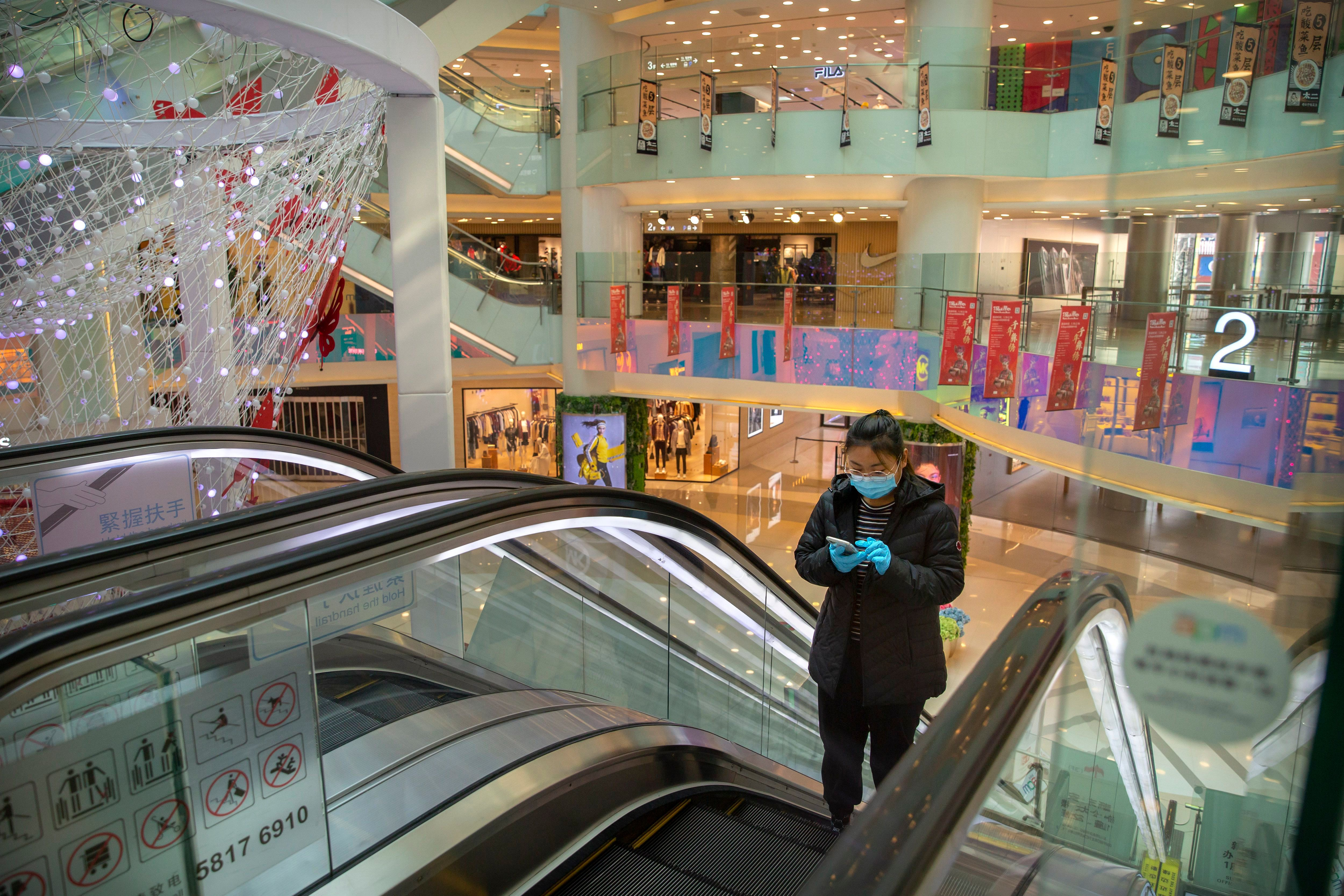 A woman wearing a face mask and gloves rides an escalator at a mostly empty shopping mall in Beijing.