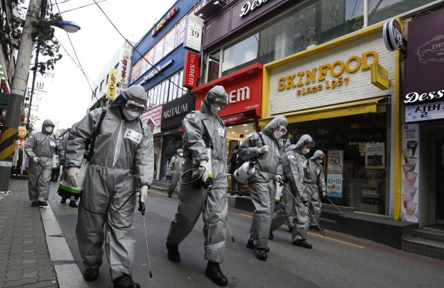 South Korean soldiers spray disinfectant in front of beauty stores Skinfood and Aritaum.