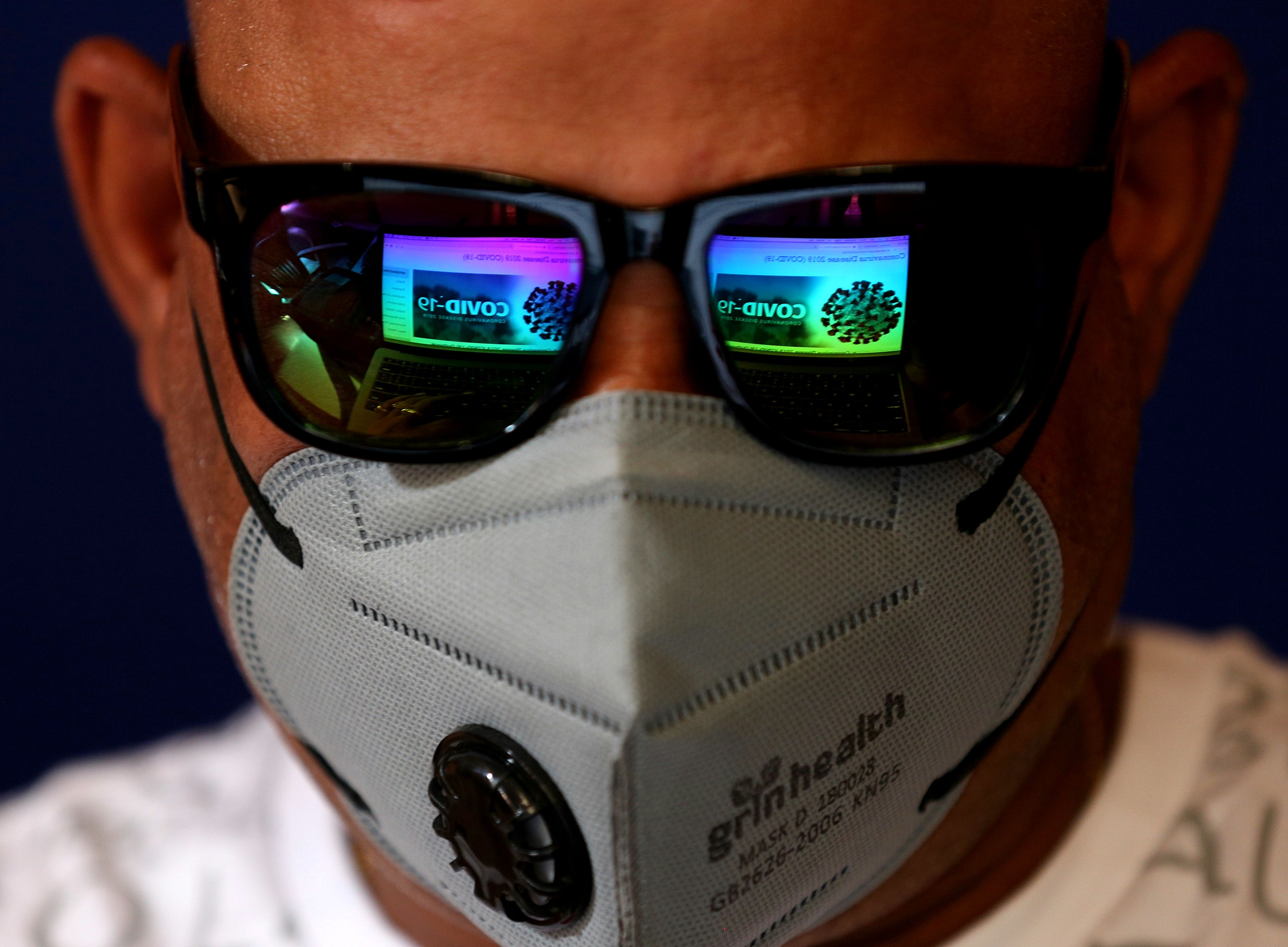 The screen of a laptop showing news about COVID-19 is reflected in the sunglasses of a man wearing a mask as a precaution against the coronavirus outbreak, in Bangalore, India, 04 March 2020. A 25-year-old software engineer from Bangalore is currently being tested after showing symptoms of a potential coronavirus infection. According to media reports, at least 15 Italian tourists and their Indian driver have tested positive for COVID-19.Preventative measures against novel coronavirus outbreak, in Bangalore, India - 04 Mar 2020