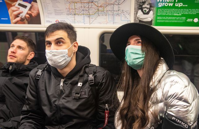 Two people wearing masks on the London Underground. Coronavirus cases across the world has today topped 100,000 and the Uk's Chief Scientific adviser has warned that it has now become a 'global epidemic'.Coronavirus -06 03 2020