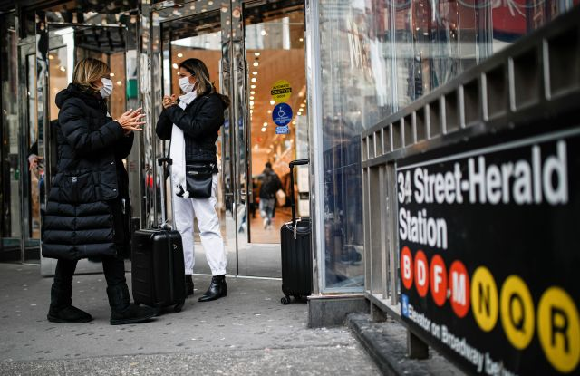 Shoppers wear face masks and sanitize their hands on the sidewalk at Herald Square in New York.