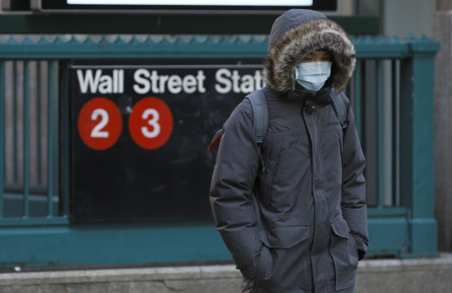 A person in a protective mask walks past the Wall Street subway station near the New York Stock Exchange in New York, New York, USA, 16 March 2020. Stocks opened sharply lower this morning and trading was halted for 15 minutes at the opening bell as investors continue to react to the impact of the coronavirus COVID-19 pandemic.New York Stock Exchange Coronaviurus reaction, USA - 16 Mar 2020