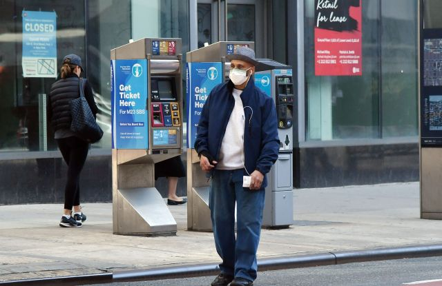 A pedestrian wearing a face mask hails a cabCoronavirus Outbreak, New York, USA - 18 Mar 2020