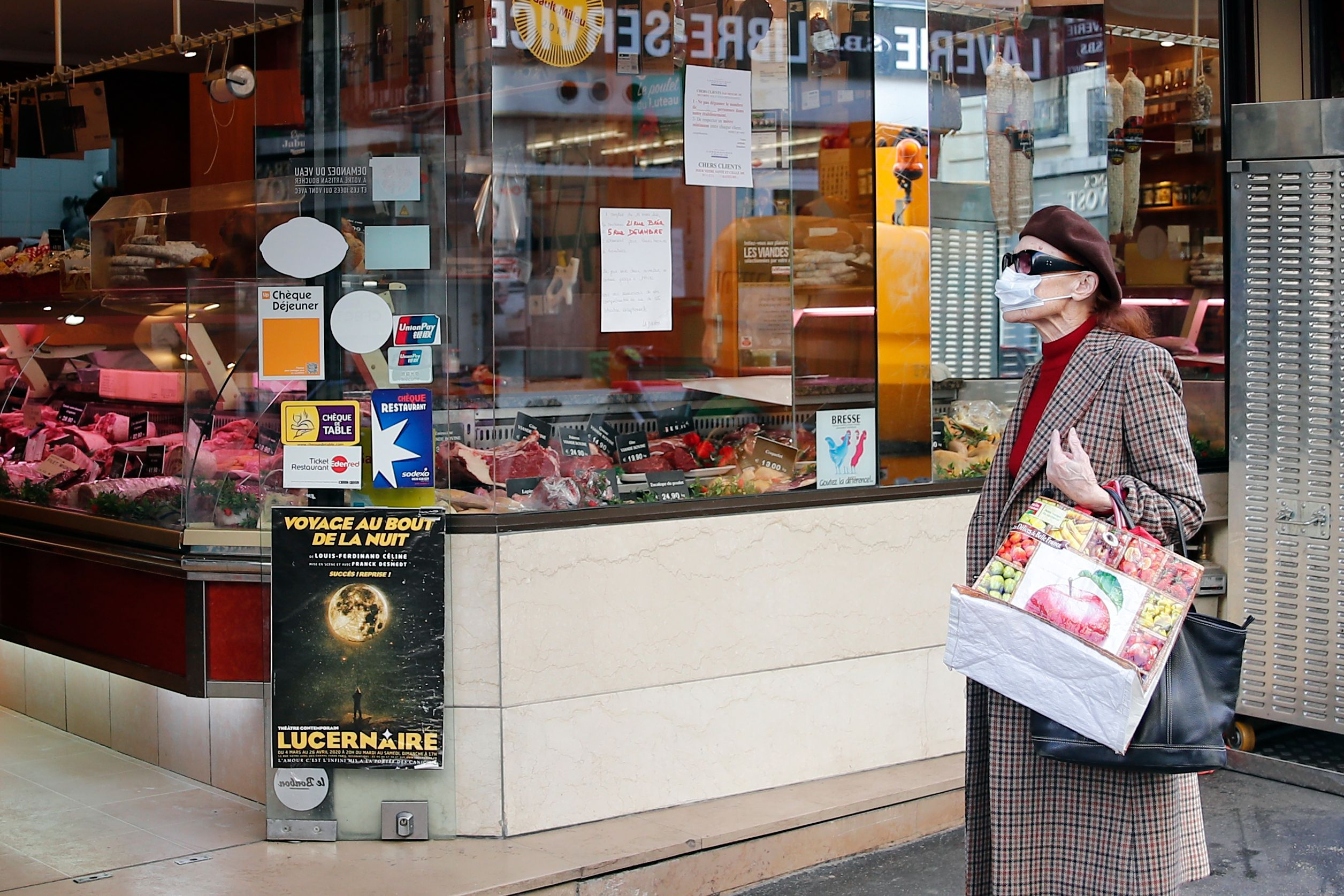 A woman walks with grocery bags amid coronavirus outbreak in Paris