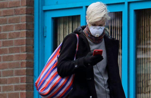 woman in mask with phone coronavirus Seattle