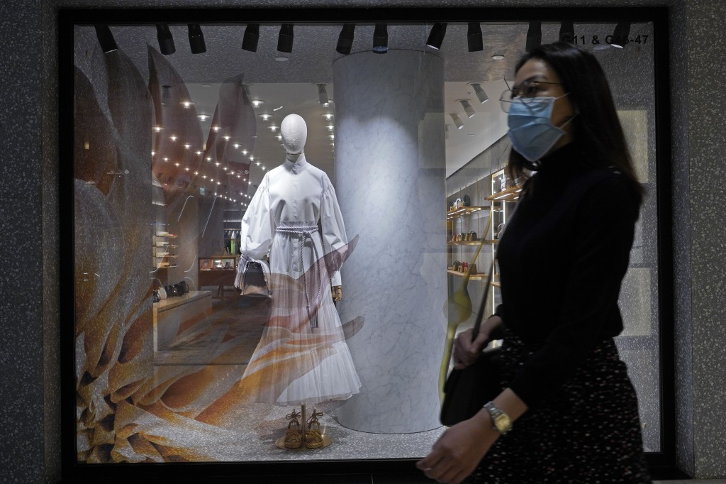 Woman wearing a face mask walks past a fashion shop in Hong Kong, . The new coronavirus causes mild or moderate symptoms for most people, but for some, especially older adults and people with existing health problems, it can cause more severe illness or deathVirus Outbreak , Hong Kong, Hong Kong - 30 Mar 2020