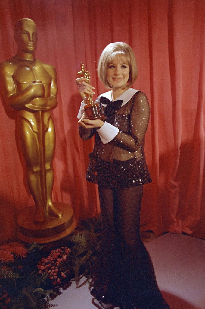 """Watchf Associated Press Domestic News Entertainment California United States APHS56920 OSCARS STREISAND 1969 Actress and singer Barbra Streisand wears a sequined Arnold Scaasi bell-bottomed sheer pantsuit as she poses with her Oscar for her role in """"Funny Girl"""" at the 41st Academy Awards in Los Angeles. Scaasi, whose flamboyant creations adorned first ladies, movie stars and socialites, died, at New York-Presbyterian Hospital of cardiac arrest. He was 85Obit Arnold Scaasi, Los Angeles, USA"""