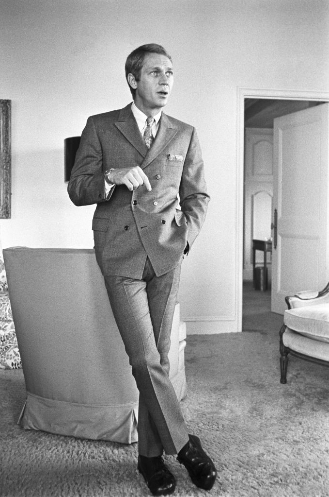 American actor Steve McQueen standing indoors, December 12, 1966. McQueen is dressed in a double breasted suit, a white button down shirt, and a paisley tie.American actor Steve McQueen standing indoors, December 12, 1966