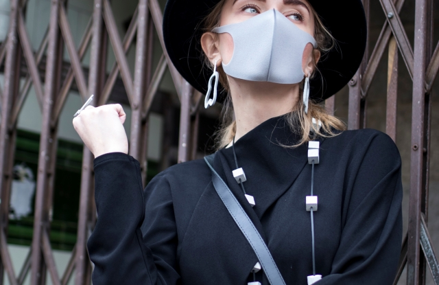 London, UK - 10 February, 2020 People wear mask for protection. Street style. Stylish woman in black dress, coat and a wide-brimmed hat wears a beige mask; Shutterstock ID 1650347188; Usage (Print, Web, Both): Web; Issue Date: March 31; Comments: WWD