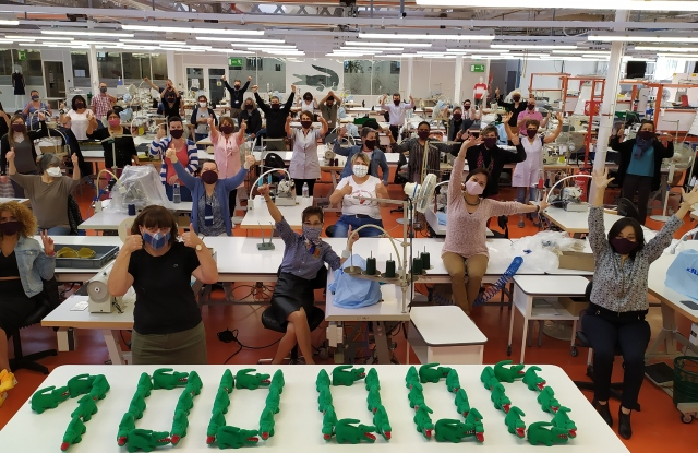 Workers cheering at the Lacoste factory in Troyes, France