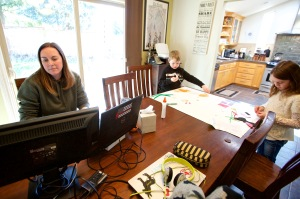 Kim Borton, left, works from home while her children Logan Borton, center, age 6 and Katie Borton, age 7, as they work on an art project in Beaverton, Ore. Borton works for Columbia Sportswear in supply chain account operations. Her children attend Hiteon Elementary school and have sent home some home work packets and emails with links for remote learning, but she has also added her own curriculum to their day to fill the voids so she can continue to work and keep the kids busyVirus Outbreak-Parents as Educators, Beaverton, United States - 17 Mar 2020