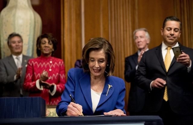 House Speaker Nancy Pelosi of Calif., accompanied by bipartisan legislators, signs the Coronavirus Aid, Relief, and Economic Security (CARES) Act after it passed in the House on Capitol Hill, in Washington. The $2.2 trillion package will head to head to President Donald Trump for his signatureVirus Outbreak Congress, Washington, United States - 27 Mar 2020
