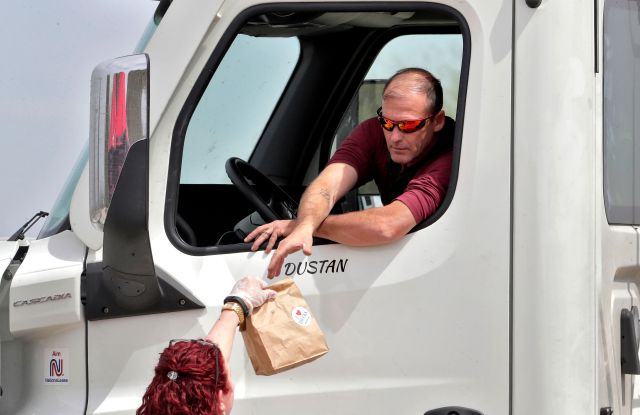 An Arizona Trucking Association volunteer gives a free lunch to a truck driver, at a rest area along I-10 in Sacaton, Ariz. The group was giving away 500 lunches from Dilly's Deli to westbound truck drivers in appreciation for delivering medical supplies, food, and other necessities during the COVID-19 coronavirus pandemic. The new coronavirus causes mild or moderate symptoms for most people, but for some, especially older adults and people with existing health problems, it can cause more severe illness or deathVirus Outbreak Arizona Truckers, Sacaton, United States - 31 Mar 2020