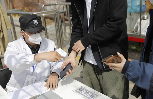 A security guard measures the body temperature of a visitor after he showed the green code to enter into 798 Art Zone in Beijing.
