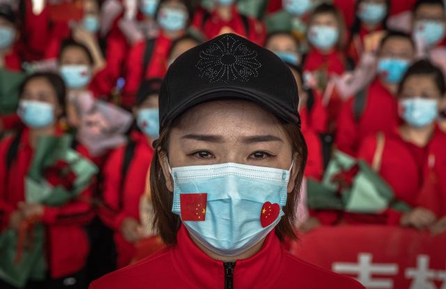 A medical worker from The First Bethune Hospital of Jilin University reacts at the airport as she prepares to leave after the lockdown was lifted, in Wuhan, China.