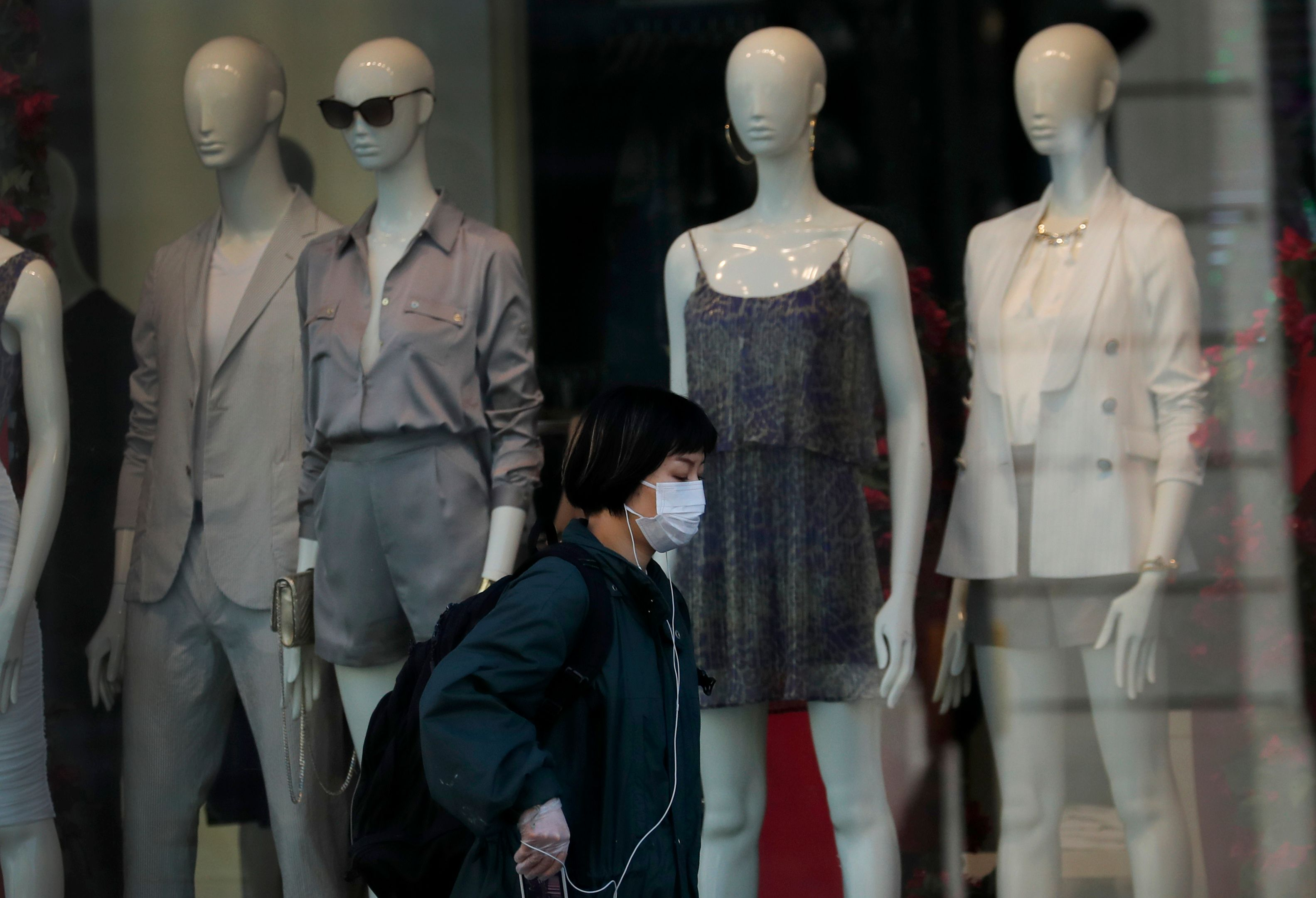 Woman wearing a face mask walks past a closed shop on Oxford Street in London, as the country is in lockdown to help curb the spread of the coronavirus, . Experts in the UK have warned that the economy could shrink by up to 35% as a knock on effect of the lockdown. The highly contagious COVID-19 coronavirus has impacted on nations around the globe, many imposing self isolation and exercising social distancing when people move from their homesVirus Outbreak Economy, London, United Kingdom - 15 Apr 2020