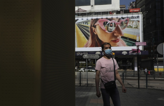A mask-wearing pedestrian walks past an advertising billboard in Tsim Sha Tsui, Hong Kong.