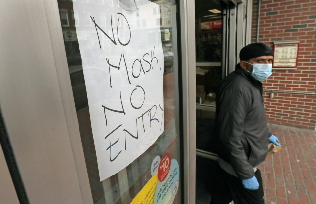 Masked shopper walks past a sign taped to the front door of a CVS Pharmacy, requesting patrons wear masks if they intend on shopping inside due to the COVID-19 virus outbreak, in Chelsea, MassVirus Outbreak Masssachusetts, Chelsea, United States - 28 Apr 2020
