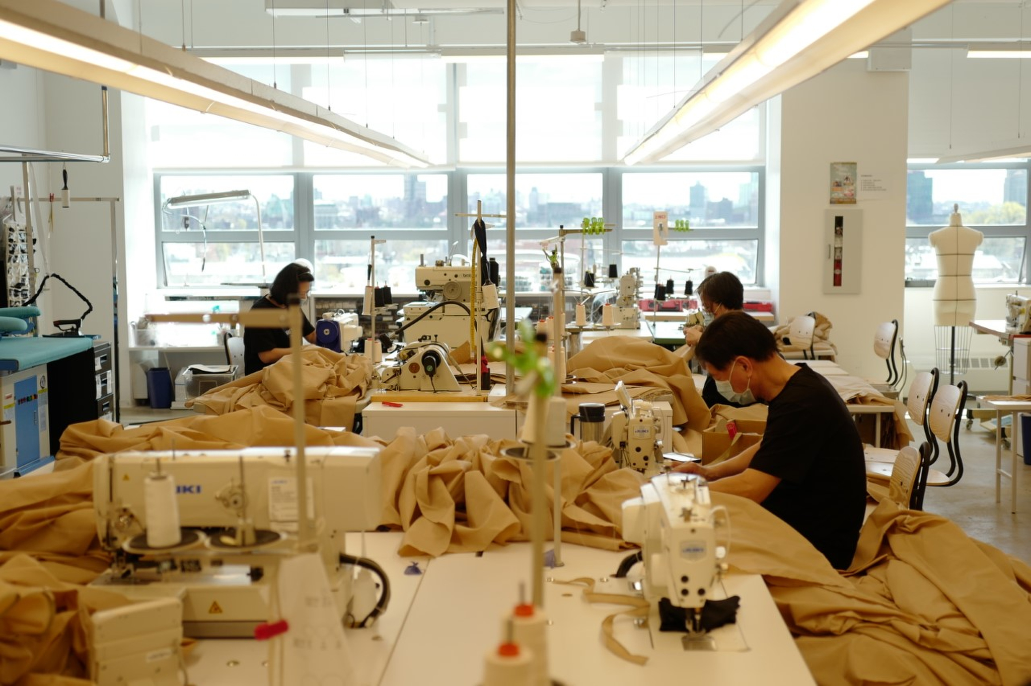 Employees at Lafayette 148 headquarters making hospital gowns, while practicing social distancing.