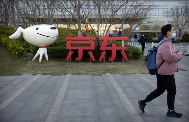 A man walks past the JD.com logo outside the company's headquarters in Beijing.