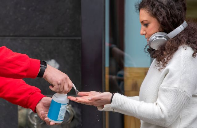 A customer receives a squirt of hand sanitizer from an employee before entering a Trader Joe's grocery store in Washington, DC, USA, 31 March 2020. District of Columbia Mayor Muriel Bowser has issued a 'stay-at-home' order to take affect 01 April 2020. The spread and containment efforts of the coronavirus COVID-19 pandemic has caused disruptions to daily life across the globe.Coronavirus COVID-19 reactions in Washington, DC., USA - 31 Mar 2020