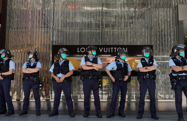 Police officers stand guard during a protest outside a luxury shopping mall Hong Kong.