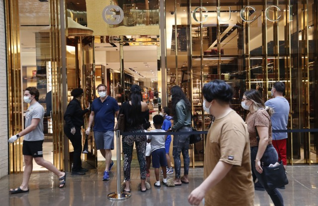 Amid concerns of the spread of COVID-19, a shopper leaves a Gucci store as other wait to enter at North Park Mall in Dallas, . Texas charged into its first weekend of re-opening the economy with residents allowed to go back to malls, restaurants, movie theaters and retail stores in limited numbersVirus Outbreak Texas Daily Life, Dallas, United States - 02 May 2020