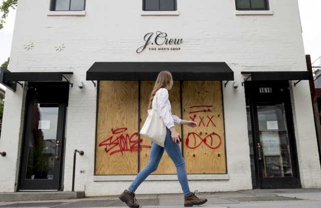 woman walks past a boarded up J. Crew