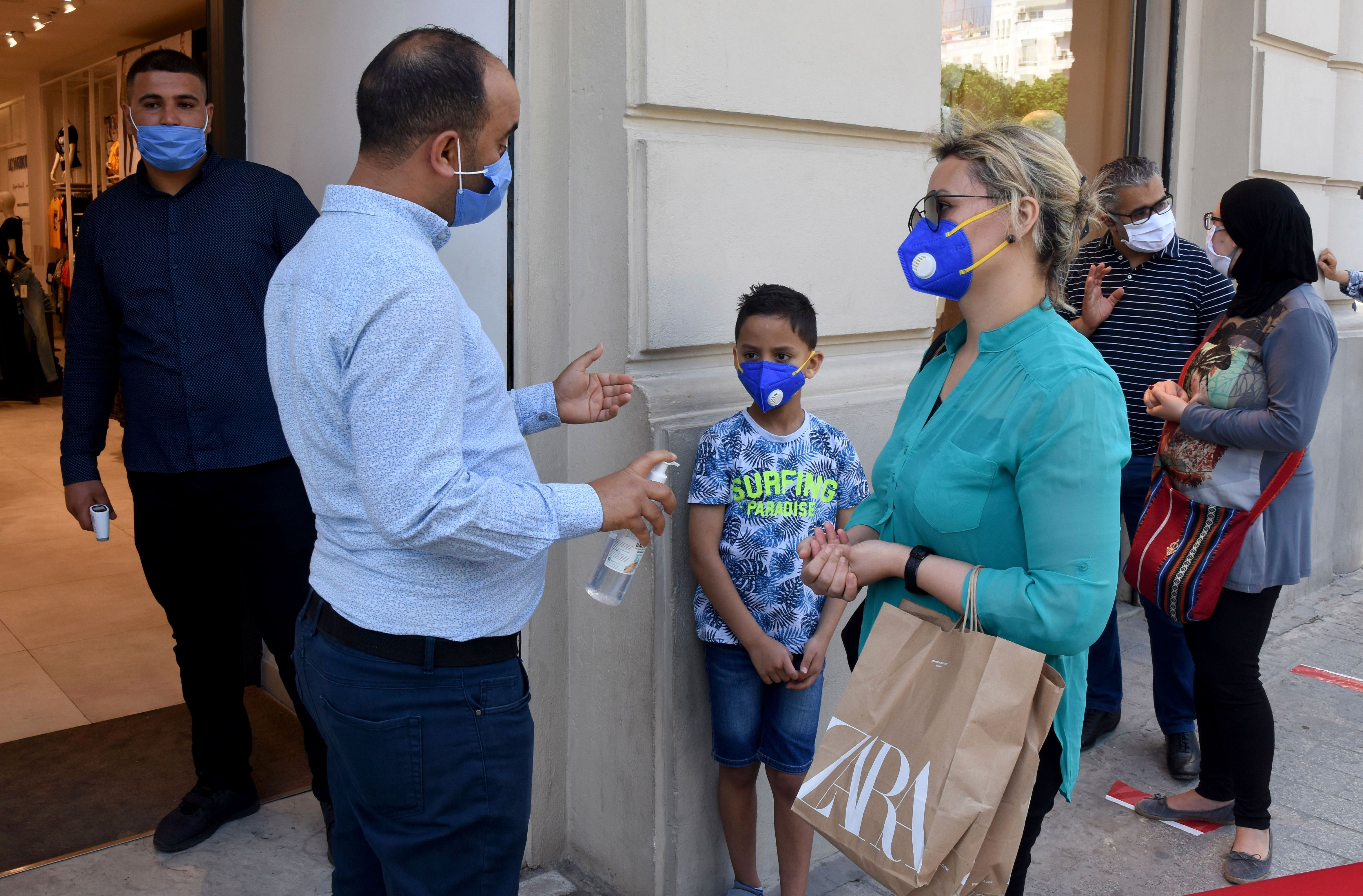 An employee sprays some alcoholic gel on customers' hands outside a fashion shop in Tunis, Monday, May, 11, 2020. Fashion shops reopen Monday in Tunisia allowing citizens to buy new outfits to celebrate the Aid next weekVirus Outbreak , Tunis, Tunisia - 11 May 2020