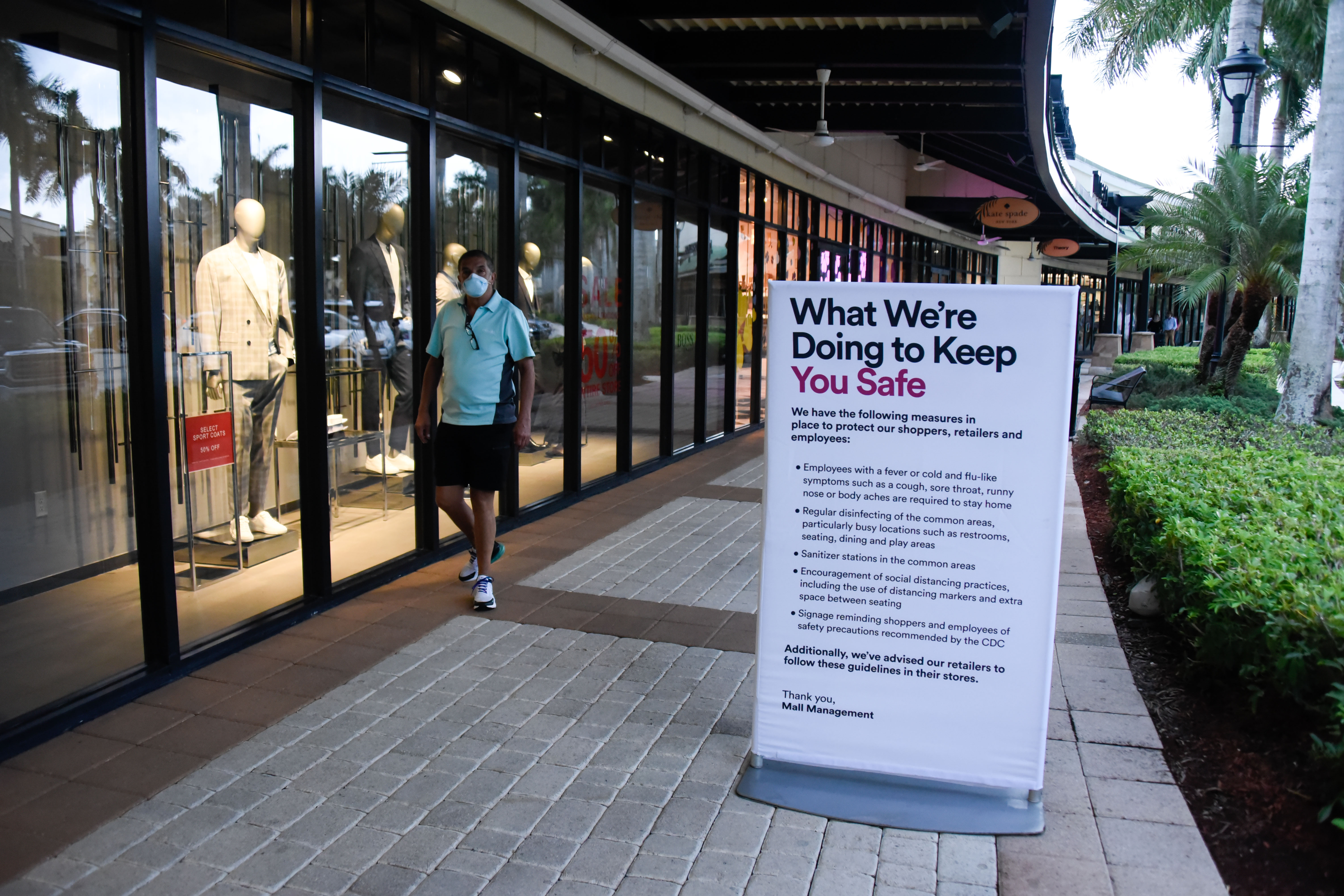 shopper in mask at mall coronavirus signrecautions in place as Phase 1 of retail reopening begins in Broward and Dade County amid the Coronavirus outbreakCoronavirus outbreak business reopening, Sunrise, Florida, USA - 18 May 2020