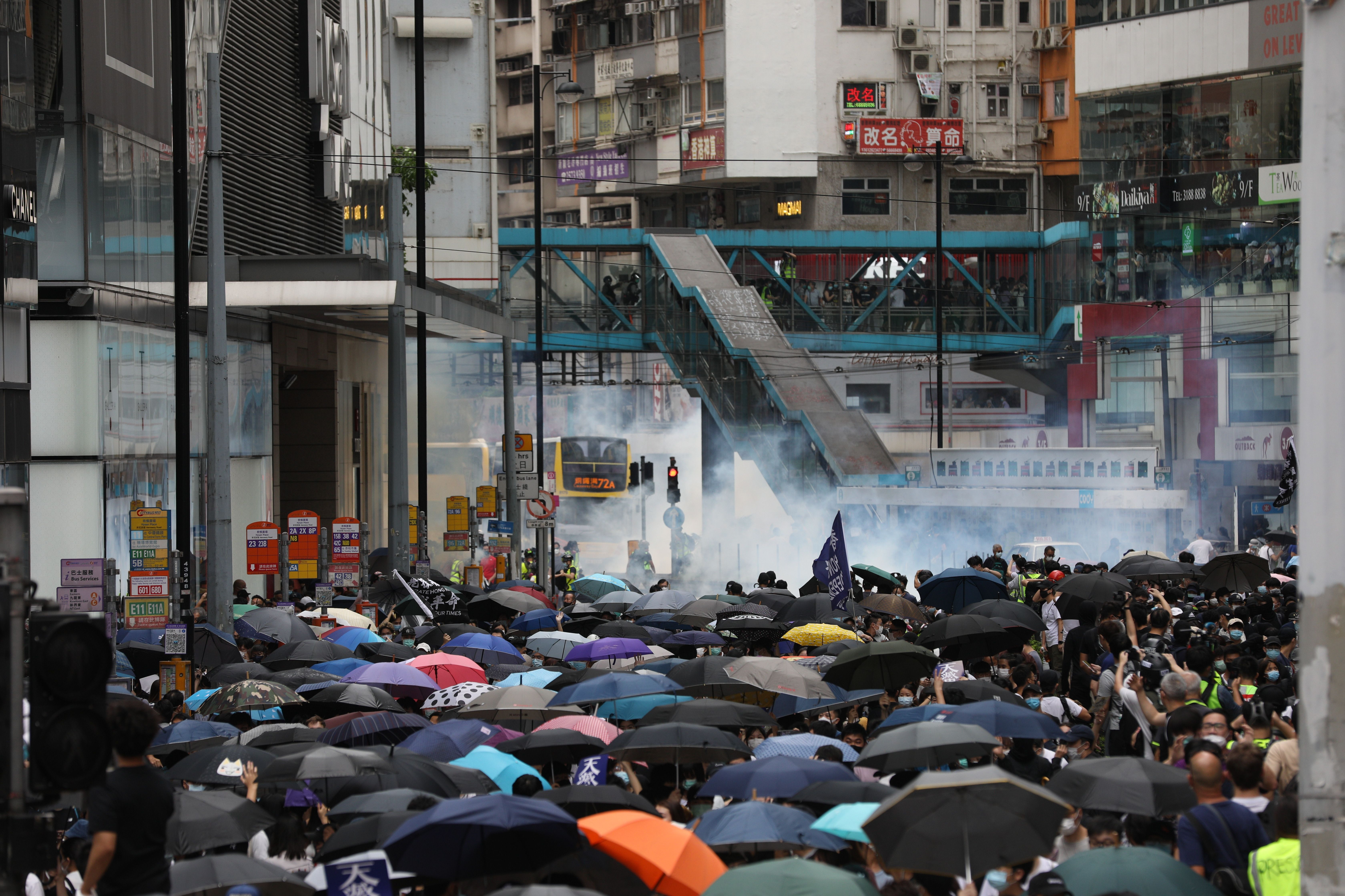 Tear gas is seen in the background as police try to disperse protesters during a rally against the implementation of a new national security law on May 24, 2020.