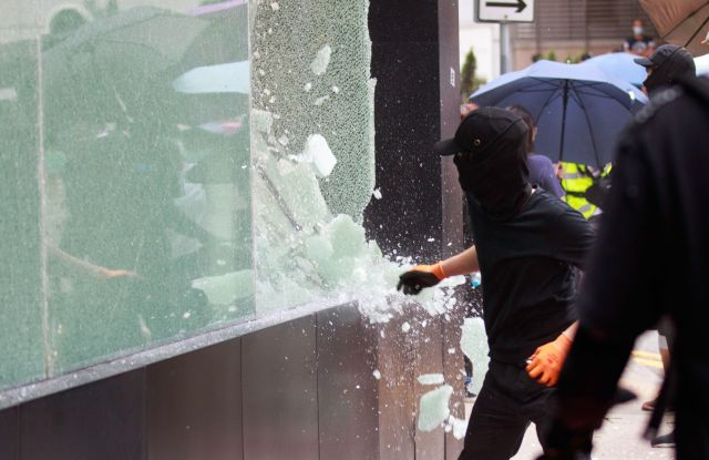 Protesters break the glass of a shop which allegedly support the police during protest against the security law.Protest vs security law in Hong Kong