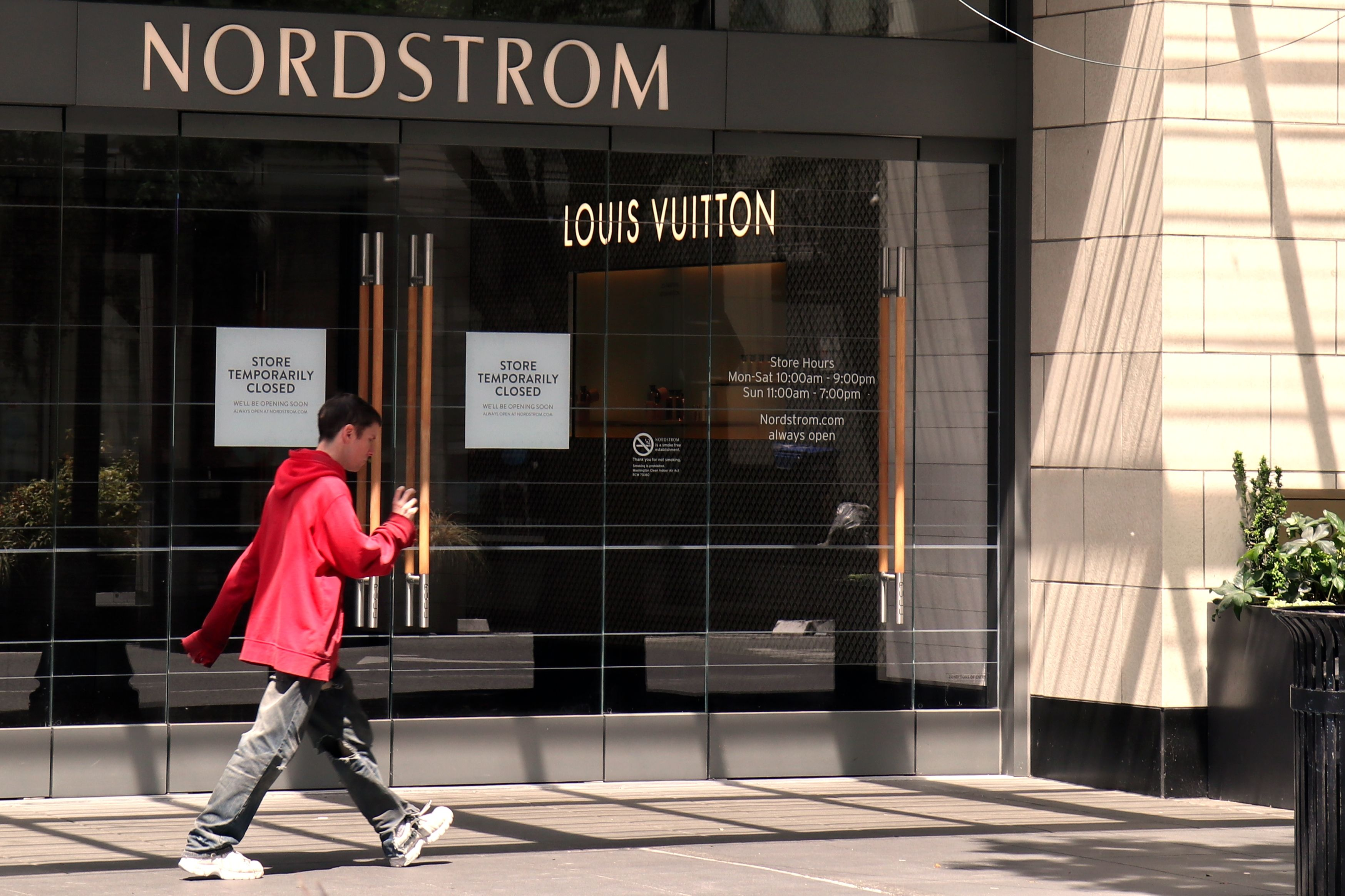 man walks by closed nordstrom store in seattle