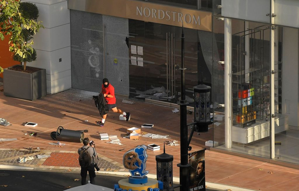 Man runs from a Nordstrom in The Grove shopping center after the store was robbed during a protest over the death of George Floyd, in Los Angeles. Protests were held throughout the country over the death of Floyd, a black man who died after being restrained by Minneapolis police officers on May 25Minneapolis Police Death , Los Angeles, United States - 30 May 2020