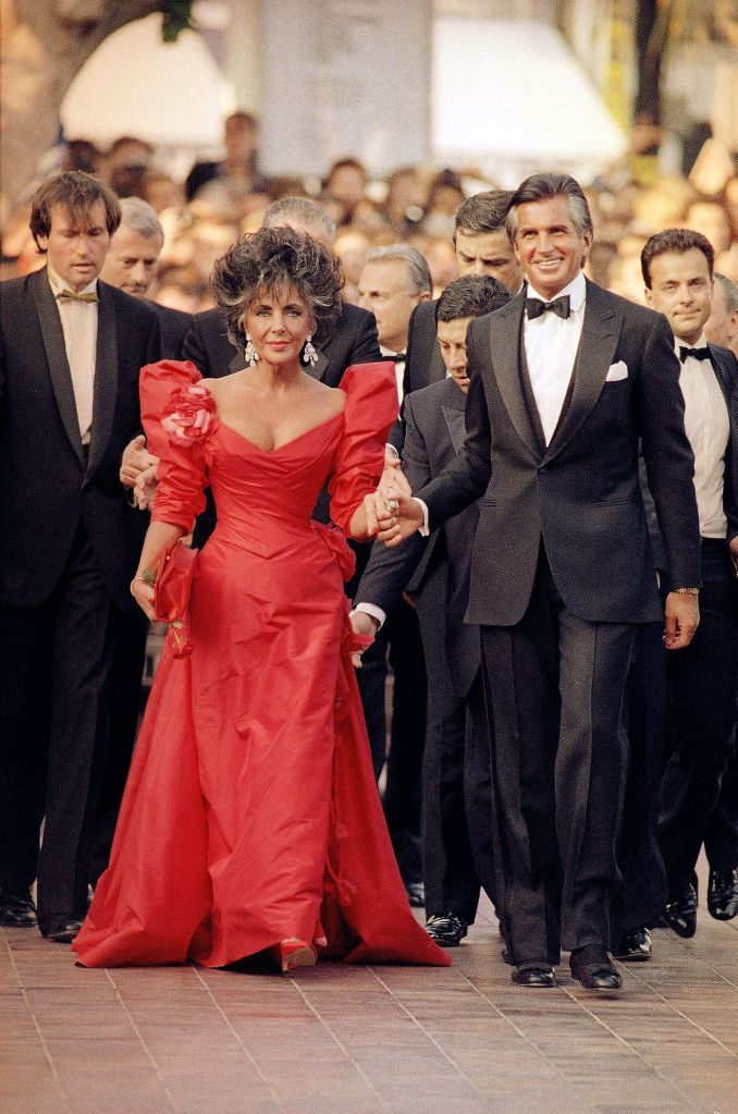American movie star Elizabeth Taylor, escorted by George Hamilton arrives at the Cannes Festival Palace in Cannes, France to attend the official gala for the Cannes Film Festival 40th Anniversary as seen in the photoElizabeth Taylor and George Hamilton, Cannes, France