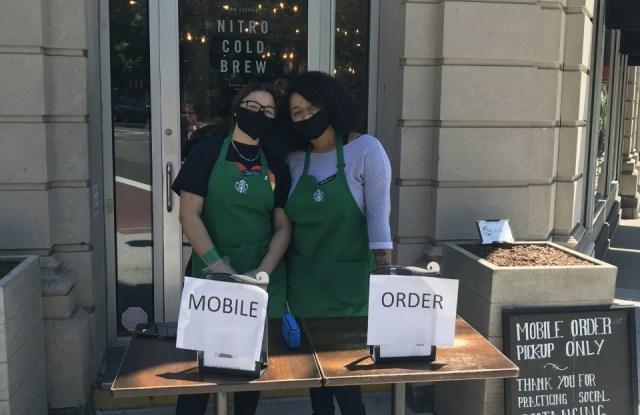 Two people outside Starbucks taking orders on Greenwich Avenue.