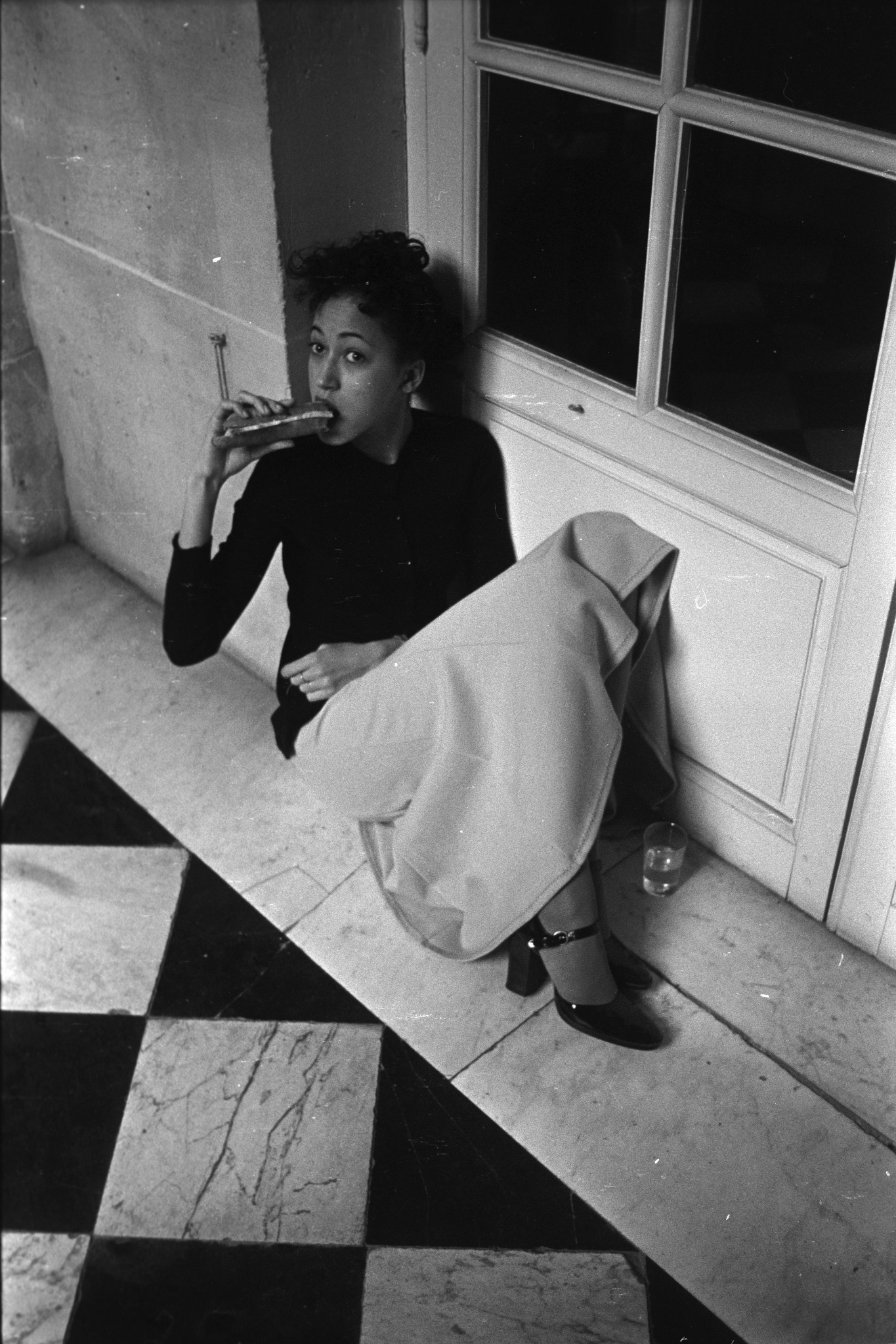 Pat Cleveland eating a sandwich backstage during the fashion show to benefit the restoration of the Chateau of Versailles, five American designers matching talents with five French couturiers at the Versailles Palace on November 28, 1973 in Versailles, France...Article title: 'One night and pouf! It's gone!Battle of Versailles, Versailles