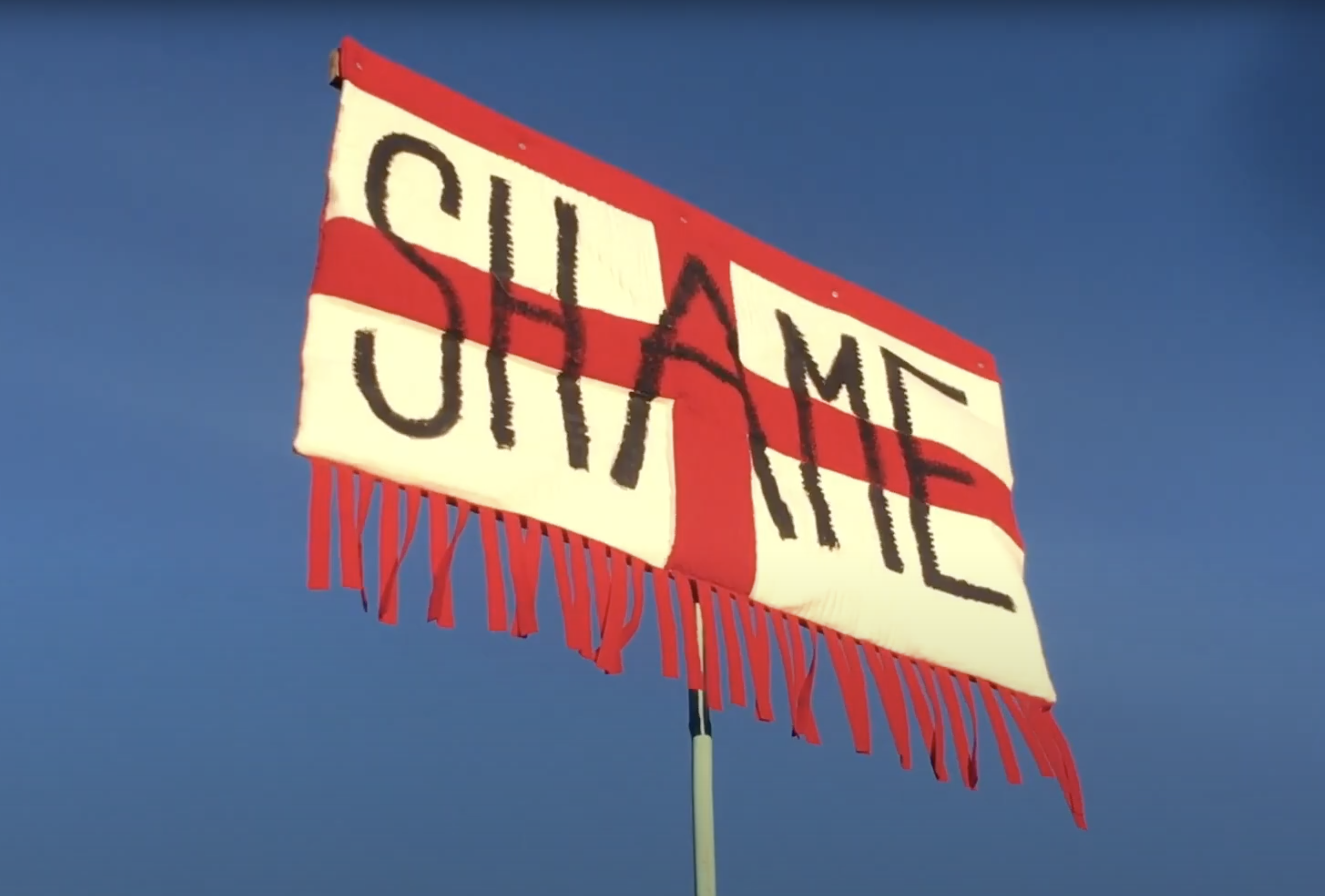 Opening scene of the Central Saint Martins BA Fashion Show 2020 video, featuring a England flag with Shame written on it, by Gus Langford.