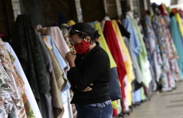 A woman browses at an apparel and textiles market.