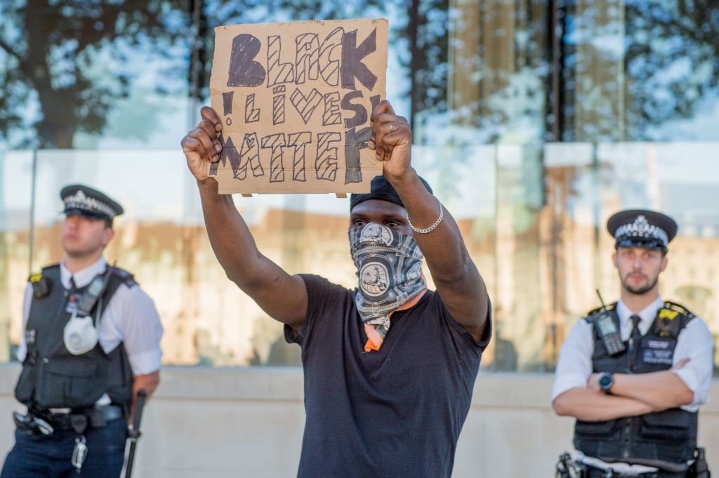 A Black Lives Matter protester outside New Scotland Yard, the headquarters of the Metropolitan Police in London in response to the death of George Floyd.