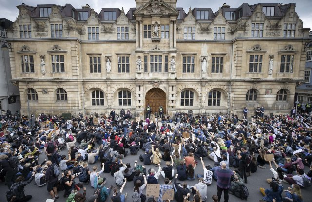 Campaigners sit in the road outside Oriel College at Oxford University, where they are calling for the removal of a statue of controversial imperialist Cecil Rhodes. Black Lives Matter protesters recently pulled down a statue of slave trader Edward Colston in Bristol town centre, following the death of George Floyd in the USACecil Rhodes protest, Oxford, UK - 09 Jun 2020